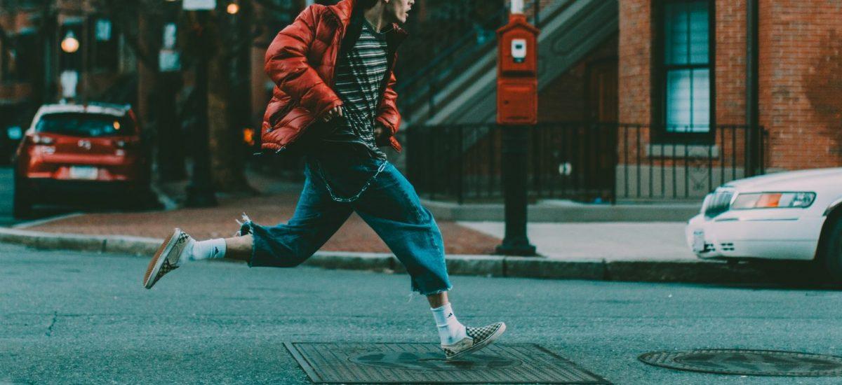 Mladý muž uteká po ulici