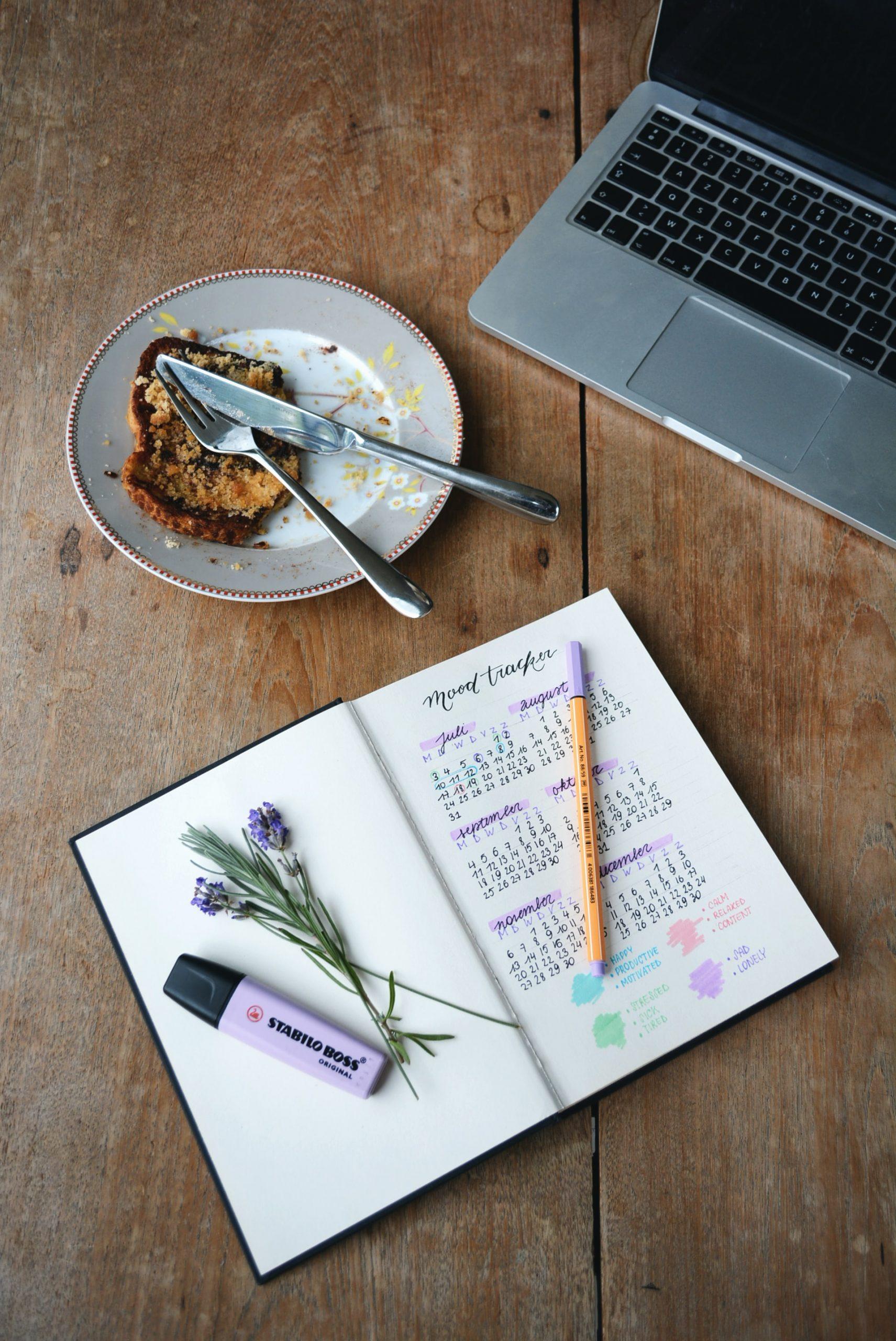 Zápisník a tanierik s príborom na kancelárskom stole