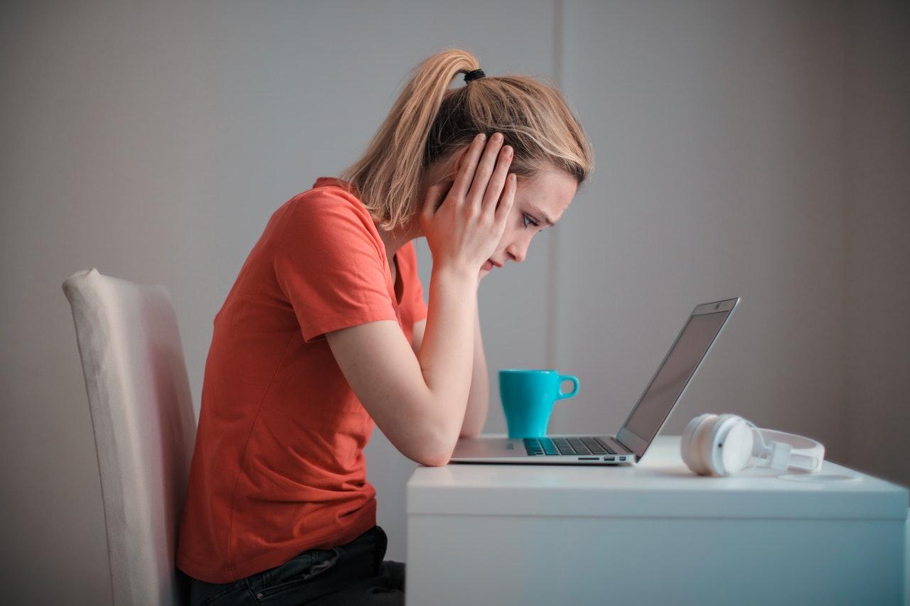 Zúfalá žena sediaca za počítačom