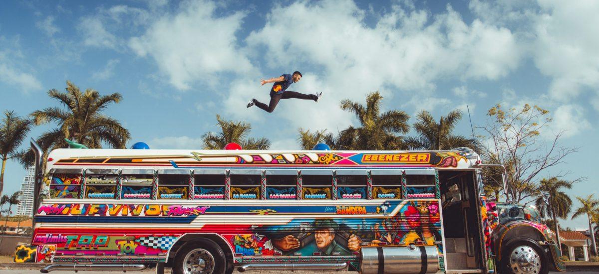 Freerunner predvádzajúci trik nad farebným autobusom v Paname