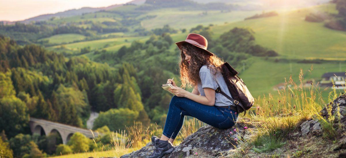 Žena na skale pozerá do zápisníka.