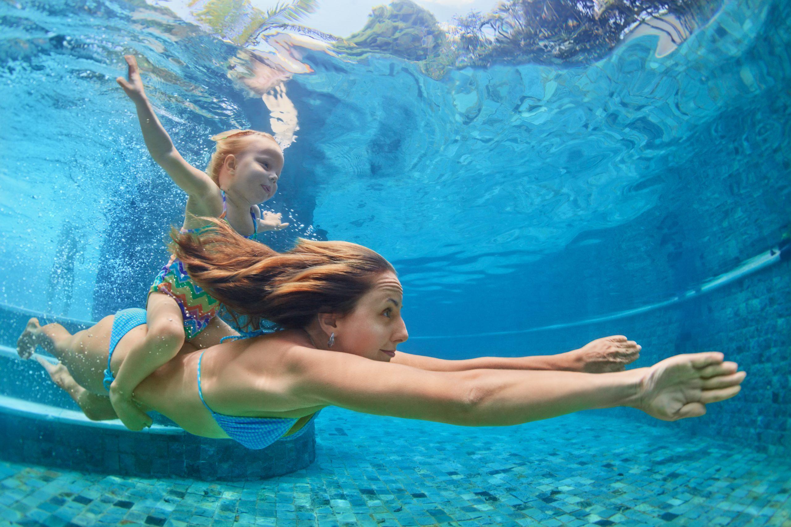 Mama pláva v bazéne s dieťaťom.