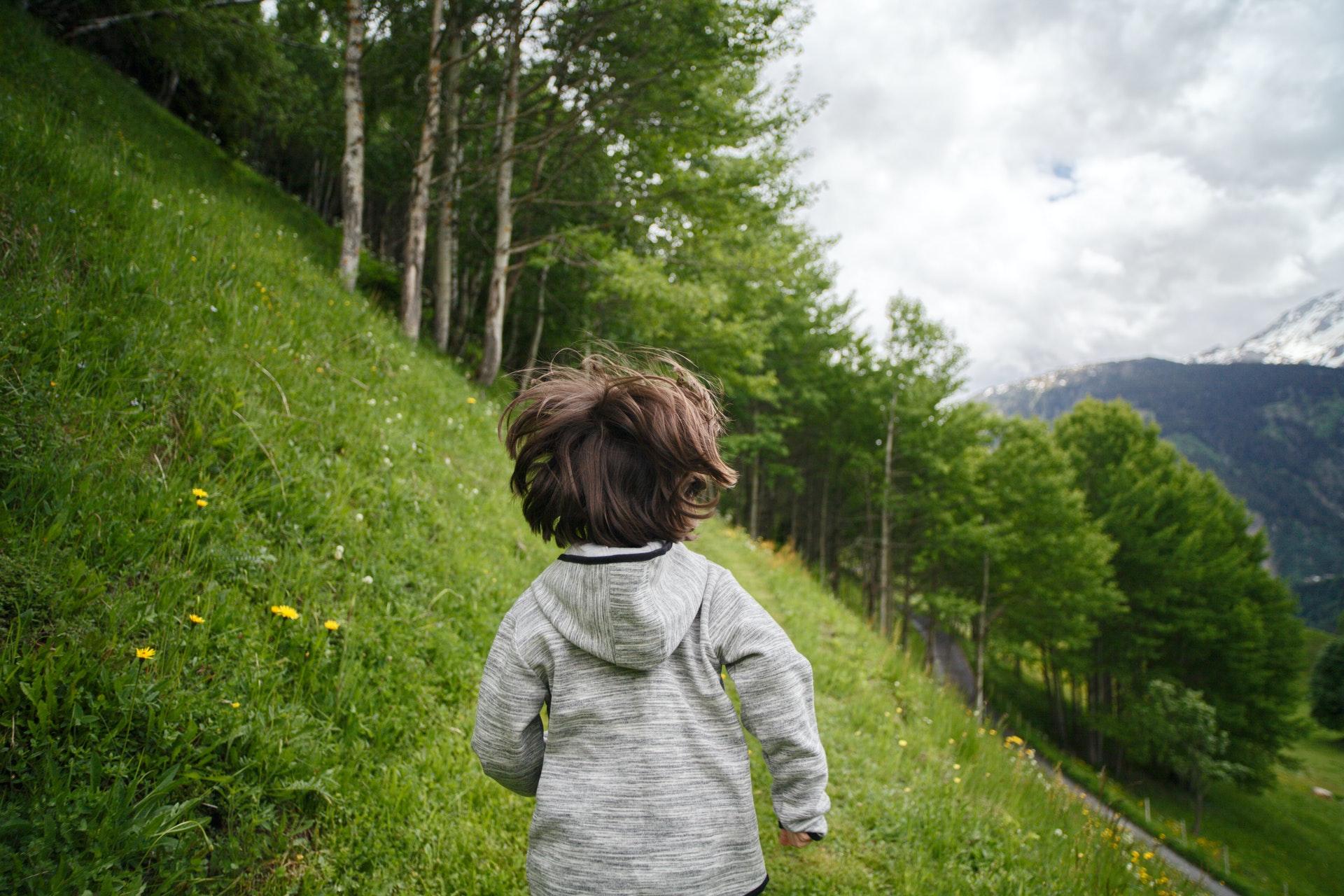 Malý chlapec bežiaci po lúke