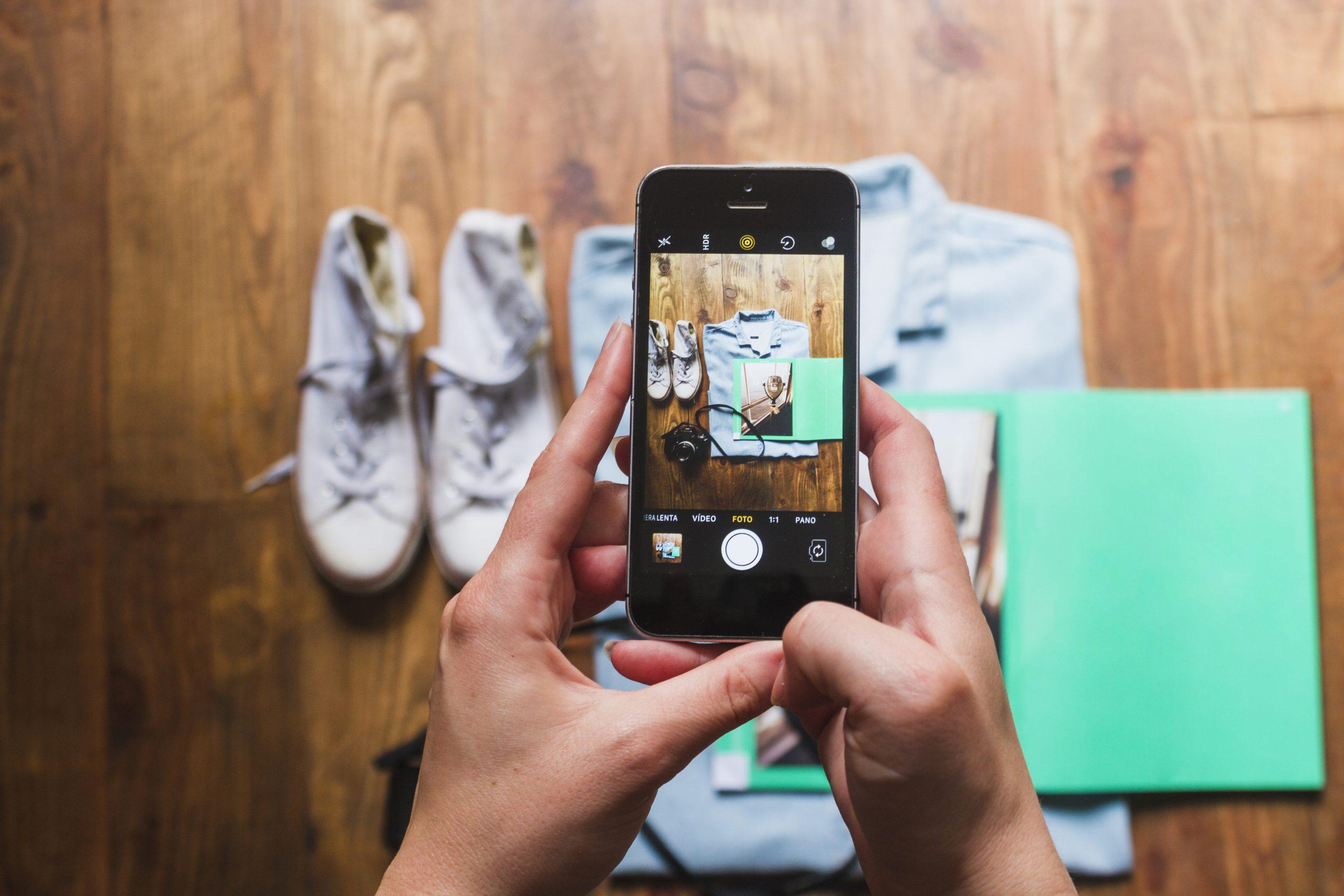 Detail na smartfón zaberajúci pohľad na tenisky, košeľu a fotoparát poukladané na zemi.