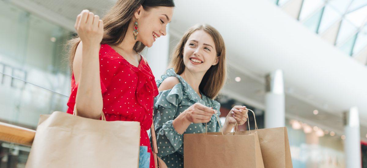 Dve dievčatá s taškami v nákupnom centre.