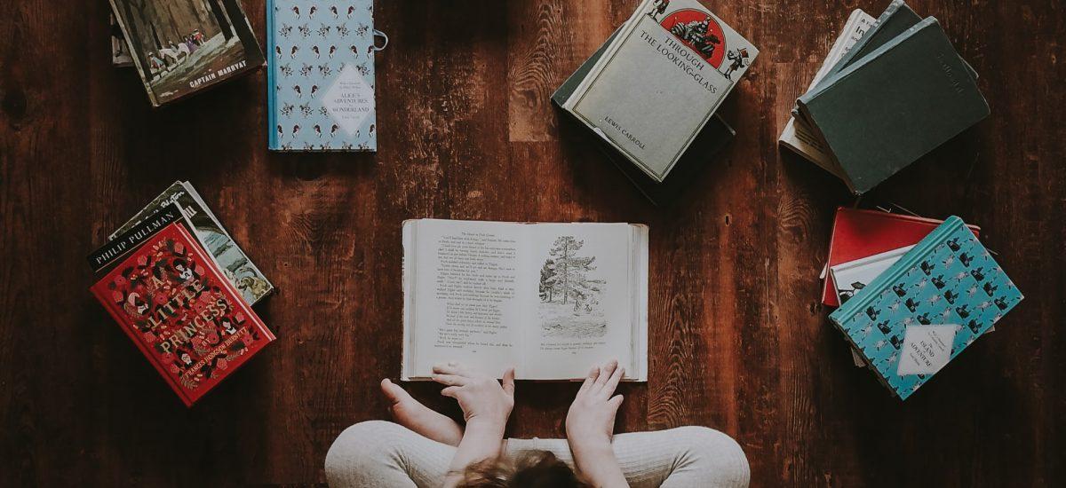Dievča číta knihu v obklopení kníh