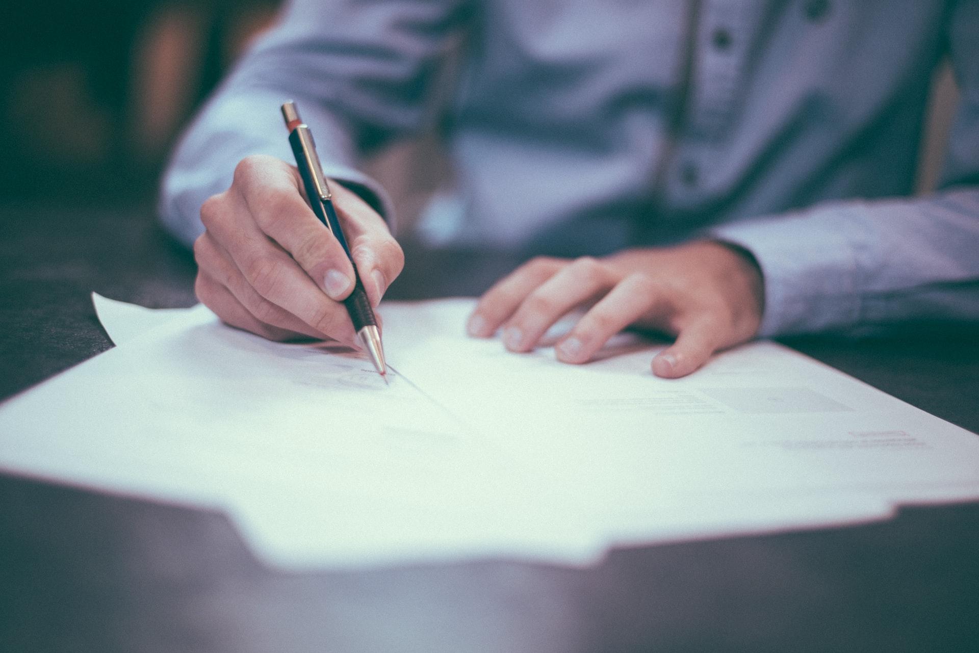 Muž podpisuje dokument