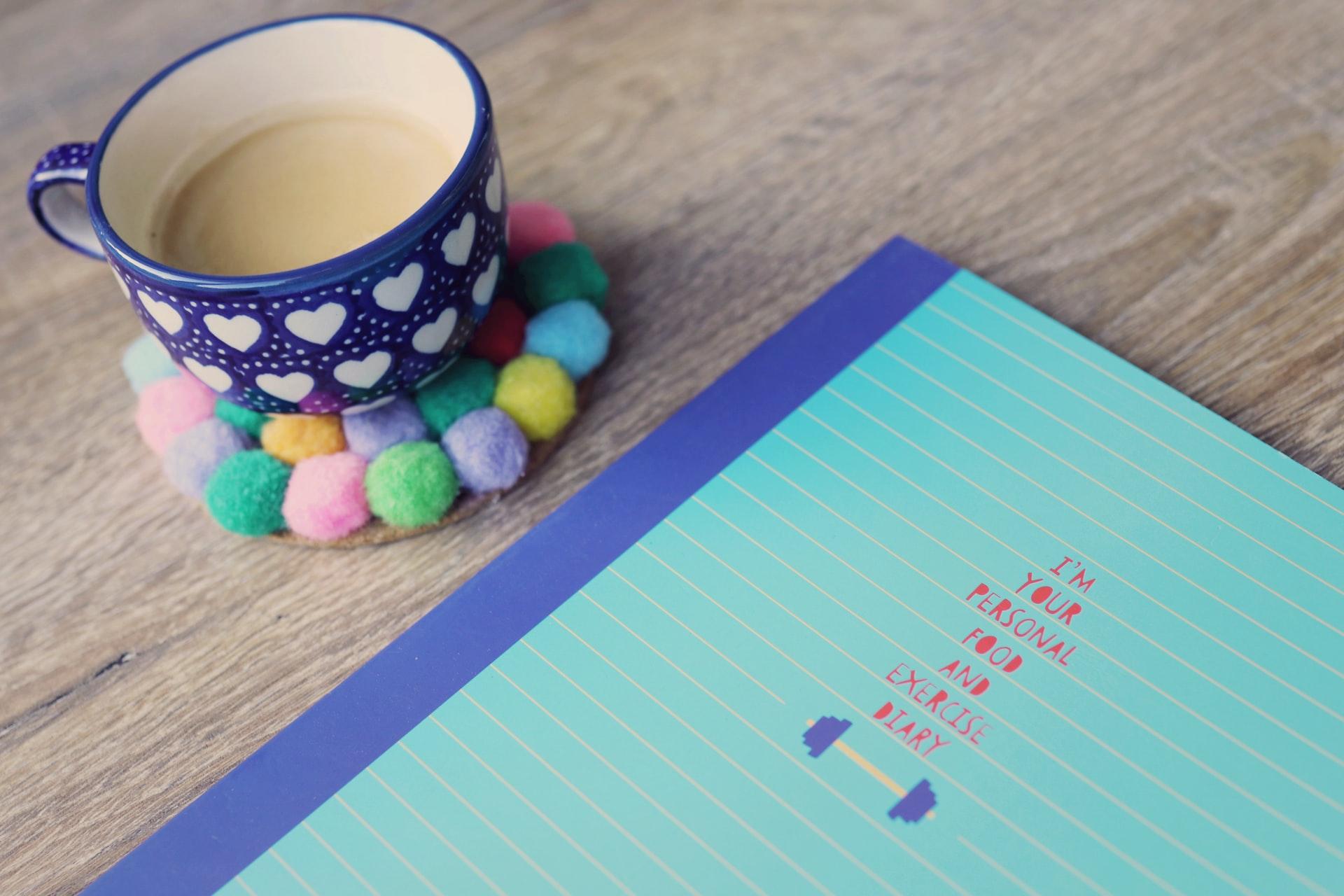 Zápisník a hrnček na stole