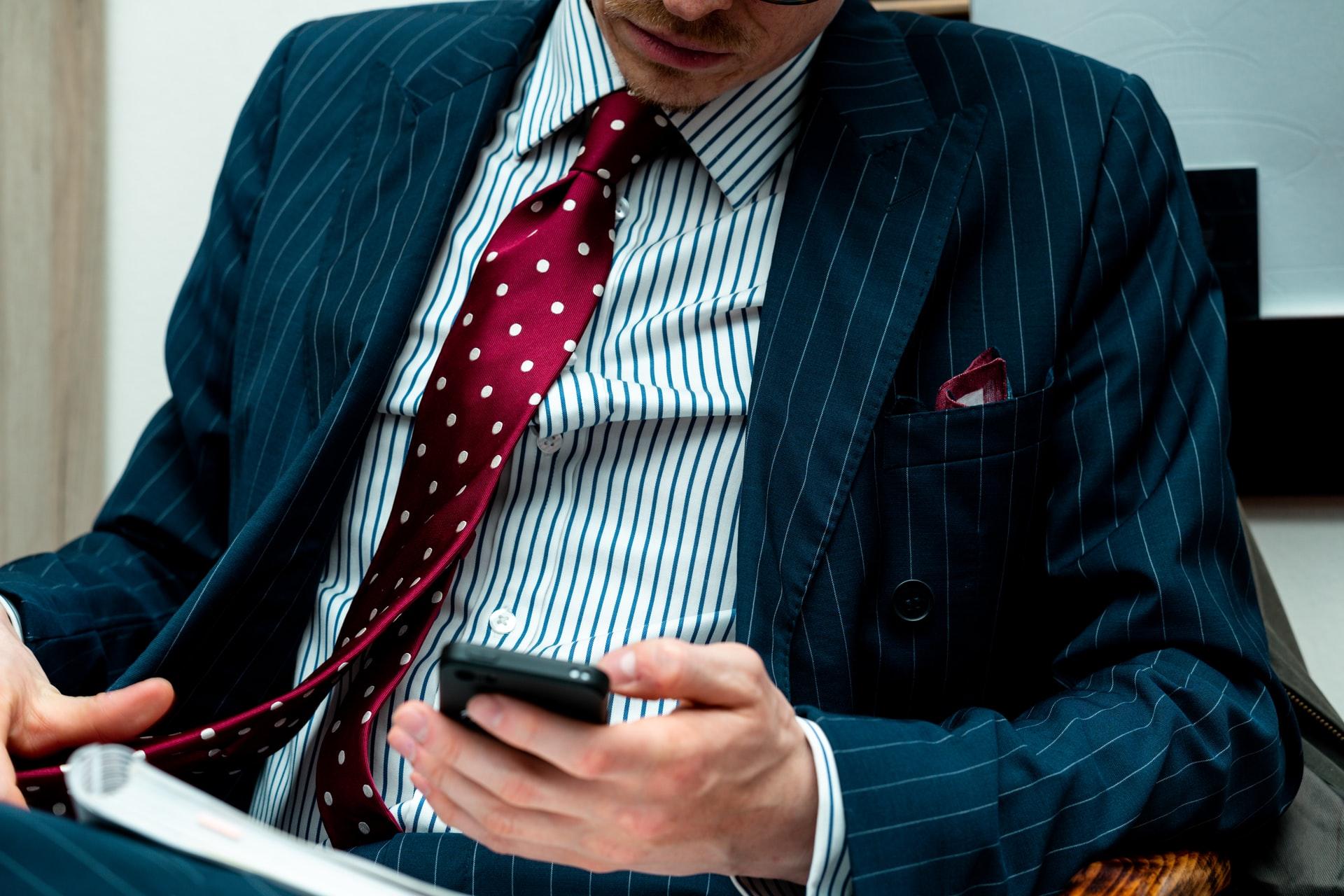 muž sedí na stoličke a drží si telefón a kravatu