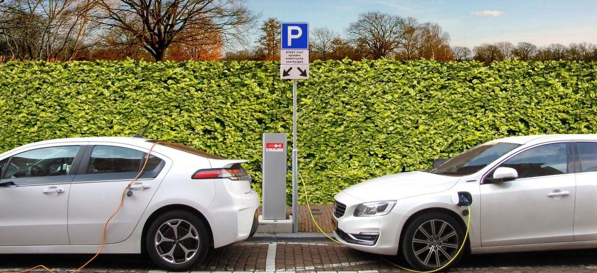 dva biele elektromobily sú napojené na nabíjačky