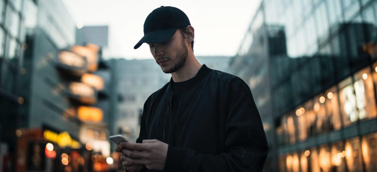 Muž sa pozerá do svojho telefónu