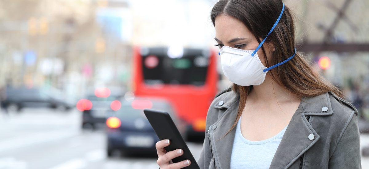 Žena s respirátorom a mobilom.