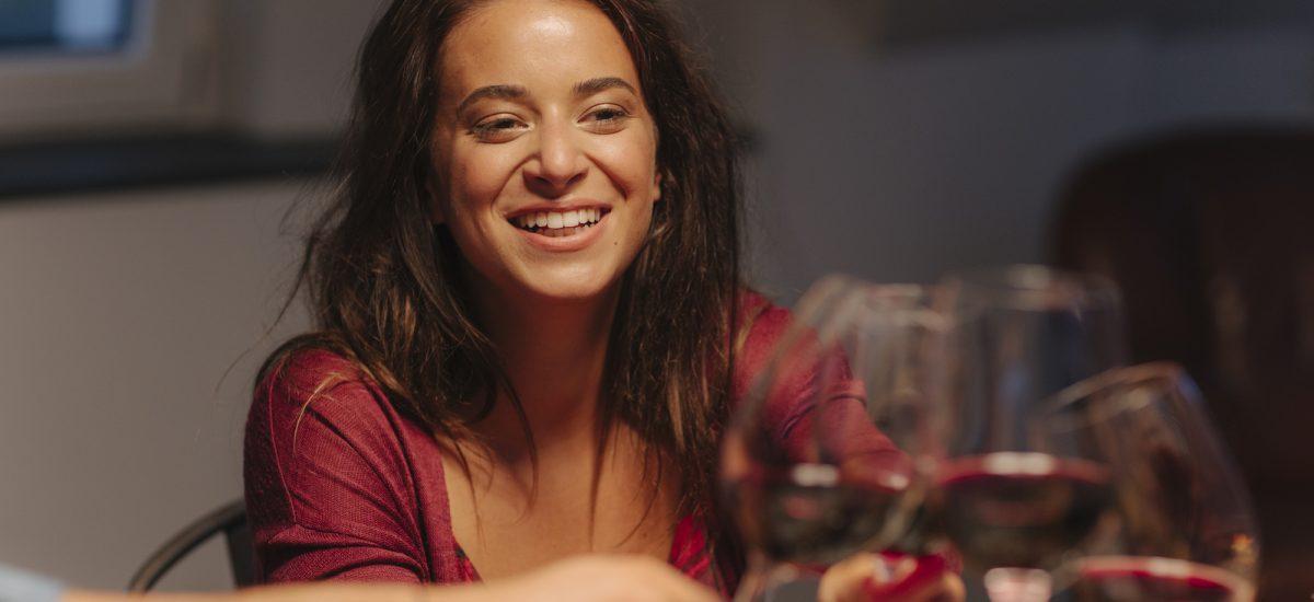 Žena si pripíja s vínom.