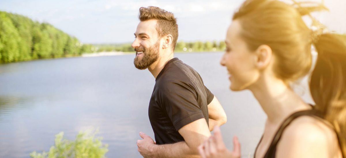 Muž a žena počas behu pri priehrade.