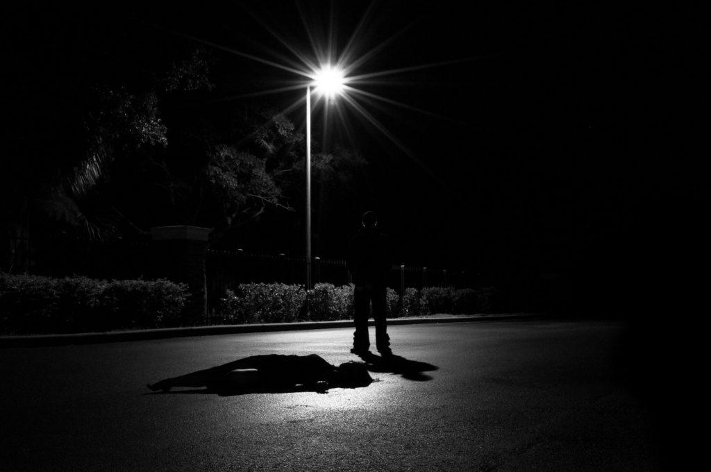 muž v tme pod lampou